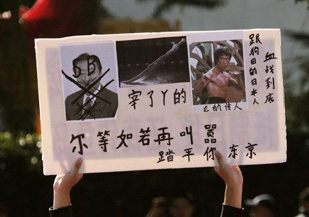 A demonstrator raises a placard during a protest on the 81st anniversary of Japan's invasion of China, outside the Japanese embassy in Beijing